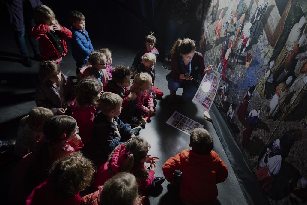Une médiatrice anime la visite Mini-Explorateur en montrant des éléments de la toile à un groupe d'enfants